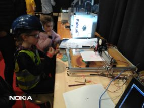 """Des enfants devant notre machine à dessiner exposée au salon """"Make It"""" de Technobel"""